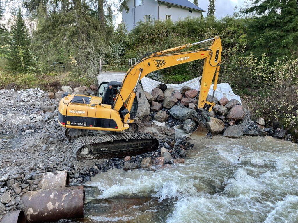 Kiviä asetellaan puretulla padolla rinteen sitomiseksi